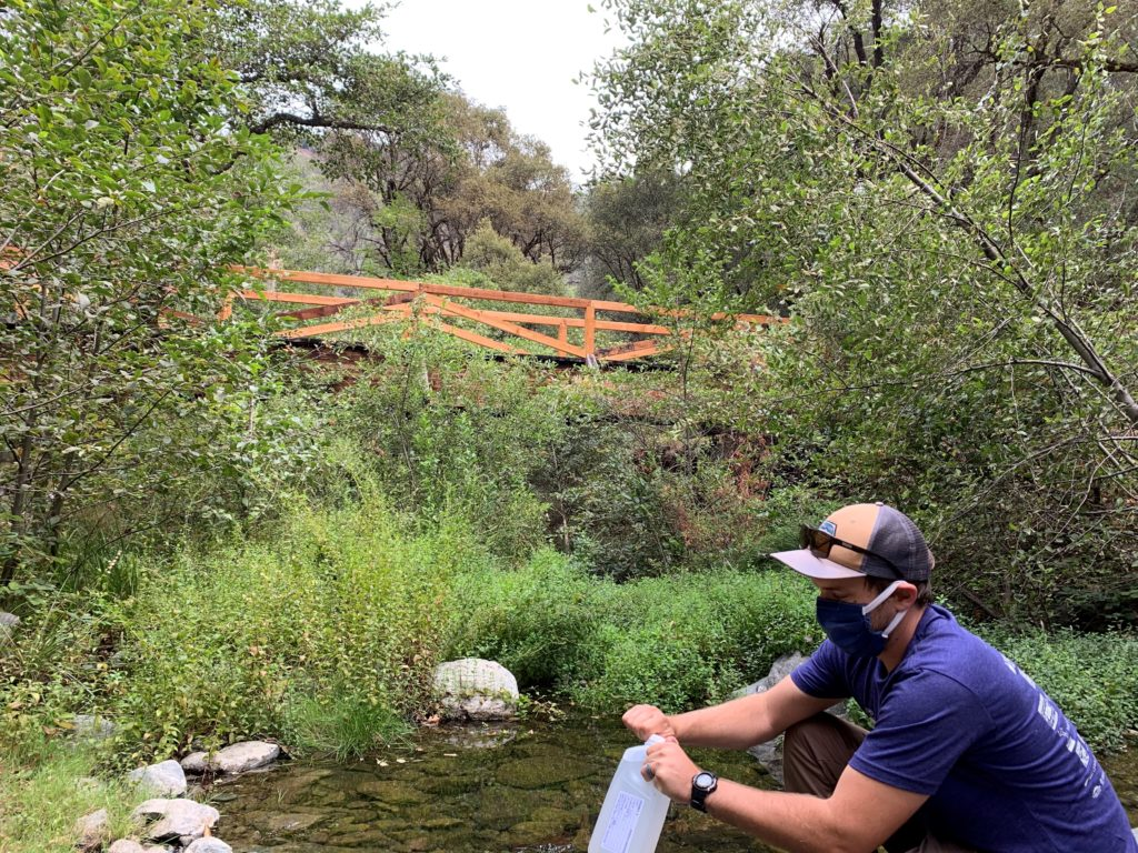 SYRCL Hydrologist, Karl Ronning, conducting River Monitoring at Rush Creek with a mask on
